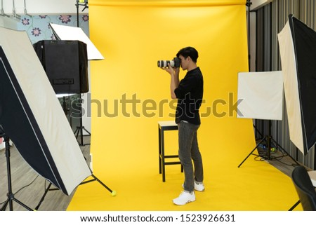 Young Professional photographer is taking picture in modern studio with photo studio background.