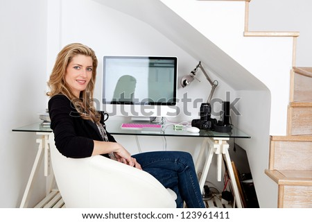 Young professional photographer working from home and sitting at her desk at home, with her camera equipment.