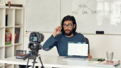 Young professional programming tutor recording video tutorial for his blog on professional digital equipment. Looking at camera and adjusting eyeglasses. Coding school. Focus on teacher. E-learning