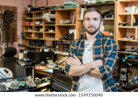 Young professional repairman of broken gadgets crossing arms by chest while standing in front of camera in his workshop