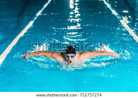 young professional swimmer in competition swimming pool  #752757274