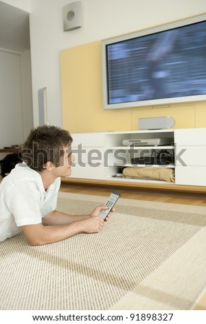 Young professional using a tv remote control while watching a flat screen tv at home.