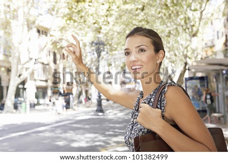 Young professional woman hitching a taxi in the financial district, smiling.