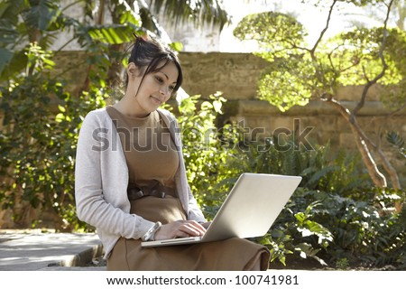 Young professional woman using a laptop computer while sitting down in a park with golden sun light.