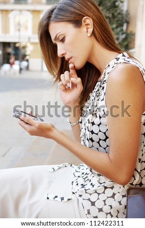 Young professional woman using a smart phone in a classic city, being thoughtful.
