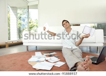 Young professional working on home finances in living room.