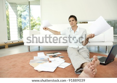 Young professional working on home finances in living room. - stock photo