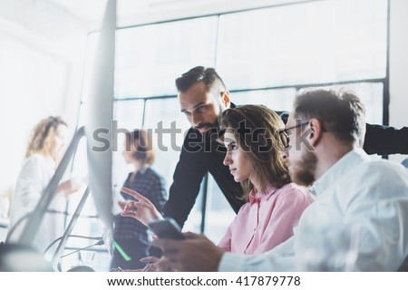 Young professionals work in modern office.Project manager team discussing new idea.Business crew working with startup.Desktop computer table,showing presentation, monitor.Blurred,film effect.