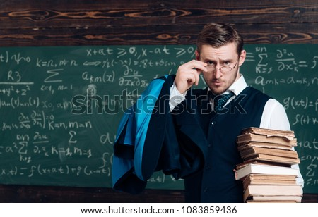 Young professor holding pile of books looking over his glasses. Aristocrat scholar in elite college.