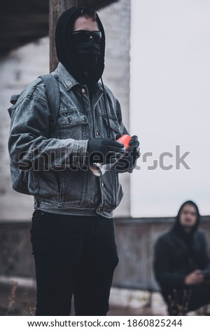 Young protesters group getting ready to make graffiti on the abandoned building. Modern styled urban hooligans. stock photo