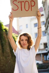 Young protesting woman in white shirt and jeans holds protest sign broadsheet placard with slogan 'Stop' for public demonstration on wall background.