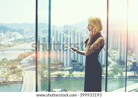 Young proud businesswoman is talking on her mobile phone with client and reading order on digital tablet, while is standing near office window with view of developed business district in China stock photo