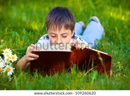 young pupil boy reading a book while lying on green grass in the park