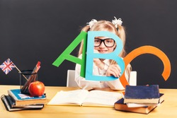 Young pupil girl wears smart eyeglasses holding colorful letters while learning English language with book before dark background