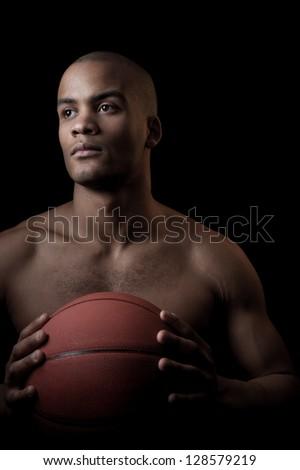 young purposeful black athlete holding basketball ball isolated on black background