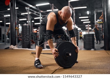 Young purposeful sportsman dresed in black stylish uniform preparing barbell for weightlifting, looking away, training in gym hall, fitness workout concept, indoor shot