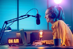 Young radio host working in the studio, she is smiling and broadcasting announcements
