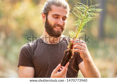 Young ranger looks forward to planting pine seedling during reforestation Stock photo ©