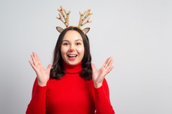 young rapturous woman with christmas deer antlers on white background. place for copy space