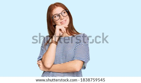 Young read head woman wearing casual clothes and glasses with hand on chin thinking about question, pensive expression. smiling and thoughtful face. doubt concept.