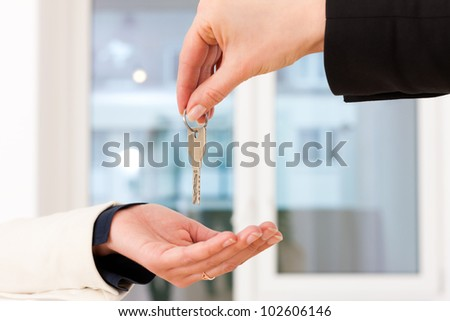 Young realtor is giving the keys to an apartment to the tenant, close-up on keys and hands
