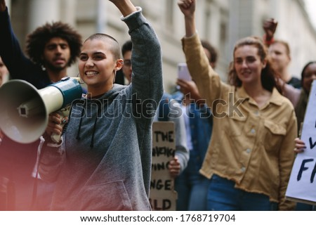 Young rebellious woman with megaphone during street protest. Female protestor yelling over a bullhorn as she participates in a street demonstration.