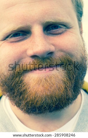 Young red bearded hipster looking into camera and smiling
