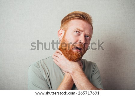 Young red bearded Man has pain in his throat