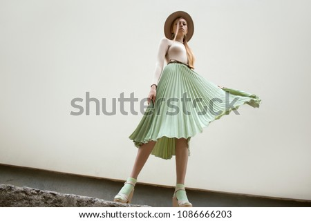 Young red hair girl in hat, dressed in beige blouse and turqoise pleats skirt, on light street backgraund.  Fashion and stylish concept. ストックフォト ©