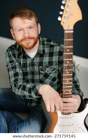 Young red hair man with red beard in plaid shirt holding a guitar on dark background