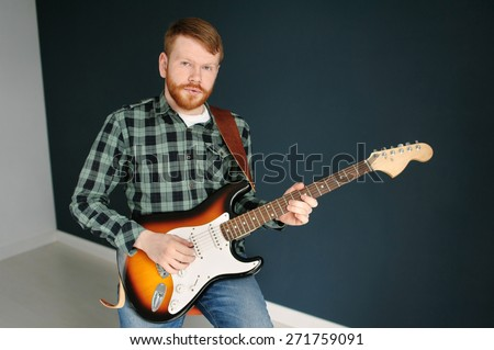 Young red hair man with red beard in plaid shirt playing guitar on dark background