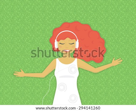 Stock Photo Young red hair woman is listening to music on grass in the park