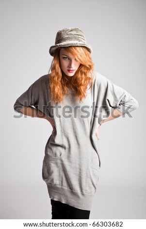 young red hair woman with hat in casual street clothes, studio shot