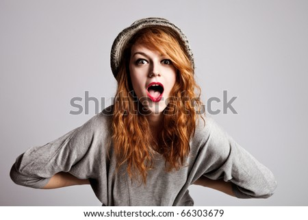 young red hair woman with surprised  expression, studio shot