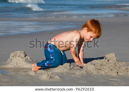 Young red haired boy playing and digging in sand on scenic beach by the sea