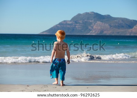 Young red haired boy playing running and jumping on scenic beach and in sea with mountains in background