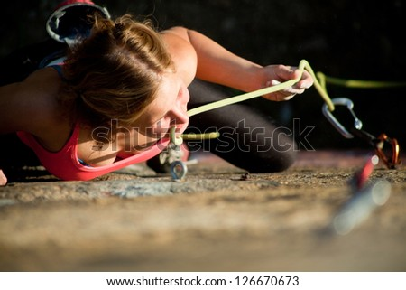 Young red-haired girl climbs on a rock with a belay