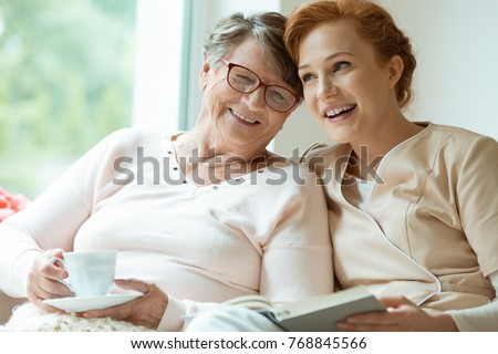 Young red haired nurse spending time with happy elder patient in nursing home