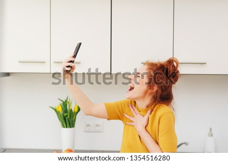 Young red-haired woman emotionally screaming or singing with her eyes shut with smartphone in her hand, as if making a selfie or video calling. Viewed from the side in home kitchen interior