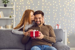 Young red-haired woman from behind hugs and kisses her beloved husband giving him a gift on this special day. Concept of gifts for birthdays, Christmas, Valentine's Day and Men's Day.