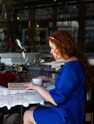 young red-haired woman in a blue dress sits on the summer terrace of a cafe and drinks coffee