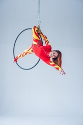 Young red-haired woman in a sports suit on the air ring makes splits. Gymnast in the air hoop in a suit of fire colors on a white background