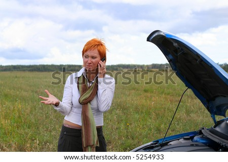 young red-haired woman with her broken car. The girl have a big problem