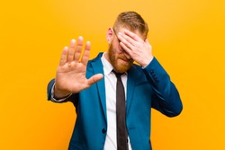 young red head businessman covering face with hand and putting other hand up front to stop camera, refusing photos or pictures against orange background