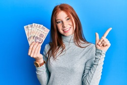 Young red head girl holding 500 mexican pesos banknotes smiling happy pointing with hand and finger to the side