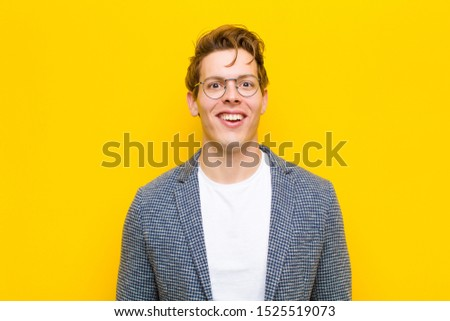 young red head man looking happy and pleasantly surprised, excited with a fascinated and shocked expression against orange background