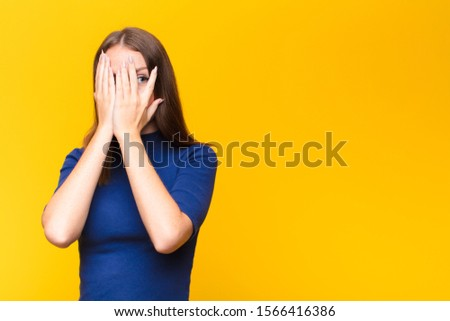 young red head woman covering face with hands, peeking between fingers with surprised expression and looking to the side against flat wall #1566416386