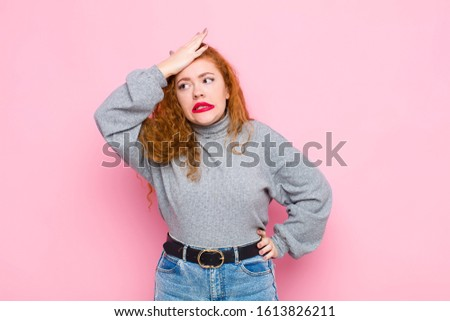 young red head woman raising palm to forehead thinking oops, after making a stupid mistake or remembering, feeling dumb against pink wall