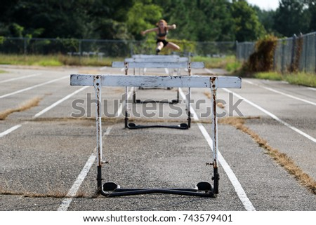 Young red headed girl practicing hurdles on old school track with old hurdles