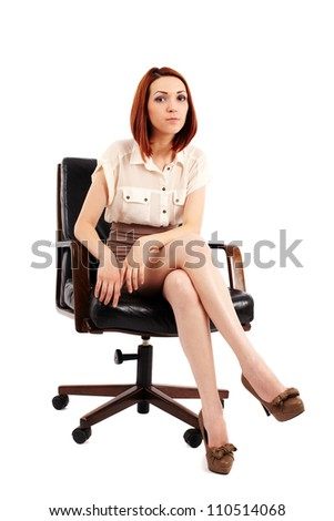 Young redhead businesswoman sitting in a chair isolated on white
